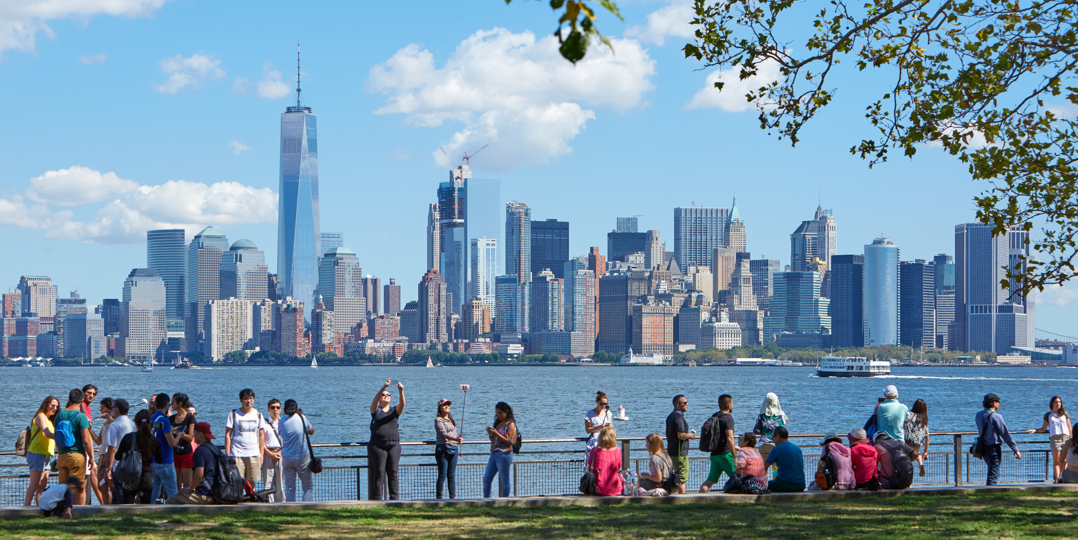 People And Tourists Shooting Selfies And Looking At New York City Skyline In A Sunny Day On In New York